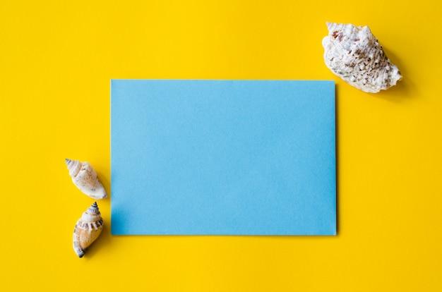 Leeres blaues blatt papier auf gelbem hintergrund mit muscheln. sommerhintergrund.