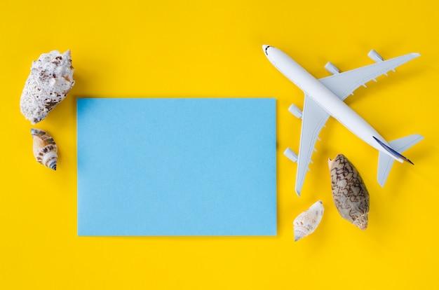 Leeres blaues papier auf gelbem hintergrund mit muscheln und dekorativem flugzeug. sommerreisekonzept.