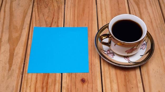 Leeres blaues papier für zitate mit kaffee auf oberem holztisch