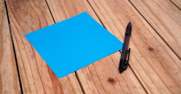 Leeres blaues papier für zitate mit stift auf oberem holztisch