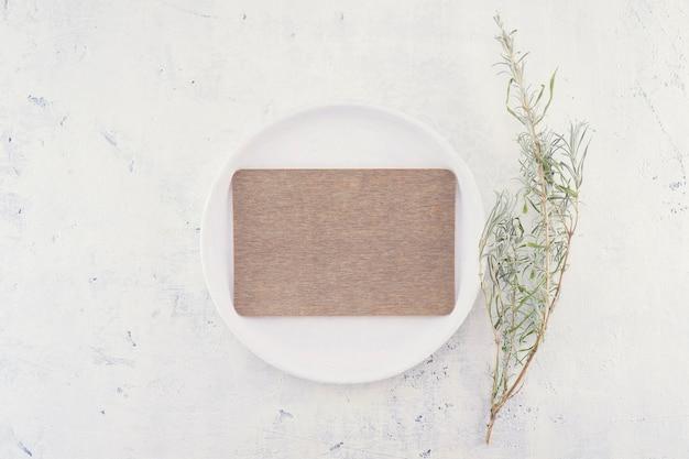 Leeres braunes leeres geschäfts- oder hochzeitskartenmodell auf weißem weinlese-teller