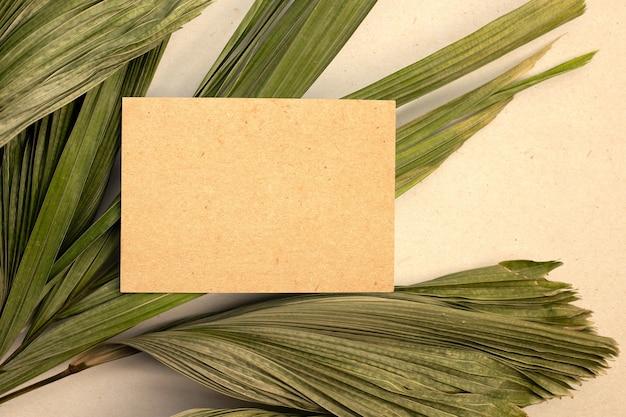 Leeres braunes papier auf trockenen blättern der tropischen palme