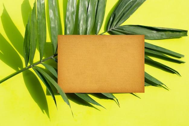 Leeres braunes papier auf tropischen palmblättern auf grüner oberfläche