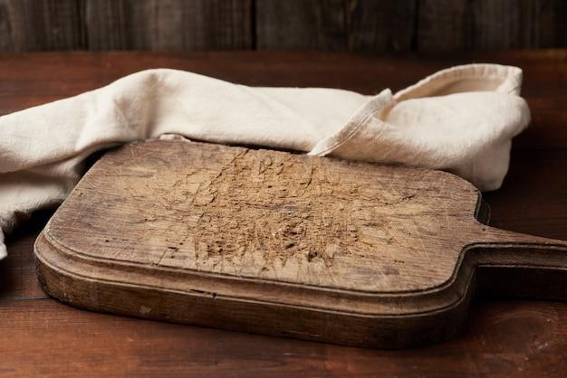 Leeres braunes vutting brett mit griff und weißem tuch