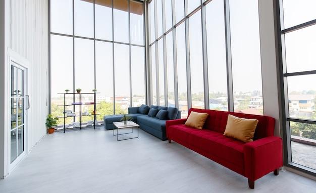 Leeres breites und hohes zweistöckiges indoor-industriedesign-fotografiestudio-wohnzimmer voller platz mit roter und grauer sofagarnitur mit holztisch in der nähe von glasfenstern mit kleinem büro im inneren.