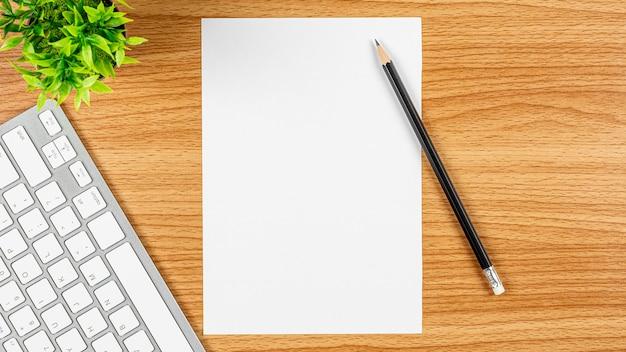 Leeres briefpapier mit einer computertastatur und einem bleistift auf hölzernem schreibtisch