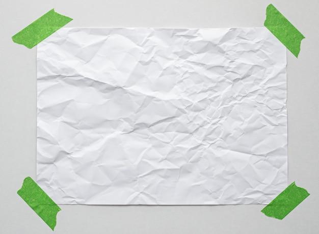 Leeres briefpapier mit klebeband an weißer wand
