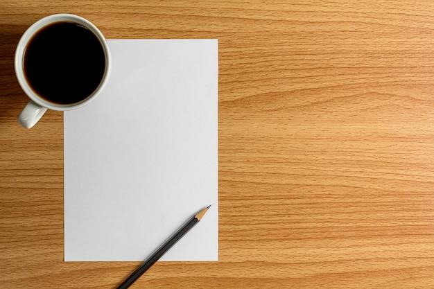 Leeres briefpapier und ein bleistift auf hölzernem schreibtisch