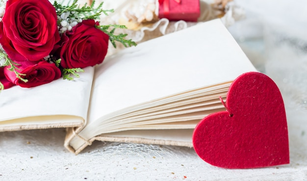 Leeres buch der weinlese mit roten rosen und dem filzherzdetail, das lto-liebesbücher bedeutet