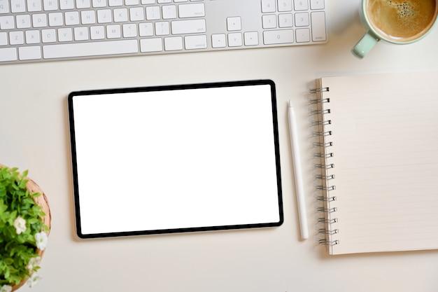 Leeres digitales tablet-bildschirmmodell mit leerer notizblock-stylus-tastatur auf weißem arbeitstisch