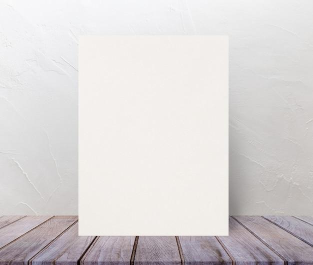 Leeres eco maserte papierplakat auf hölzerne tischplatte an der weißzementwand