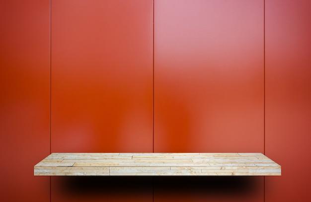 Leeres felsenanzeigenregal auf roter metallplatte shiney