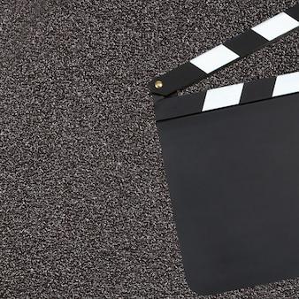Leeres filmproduktions-filmklappenbrett über dunklem hintergrund mit c