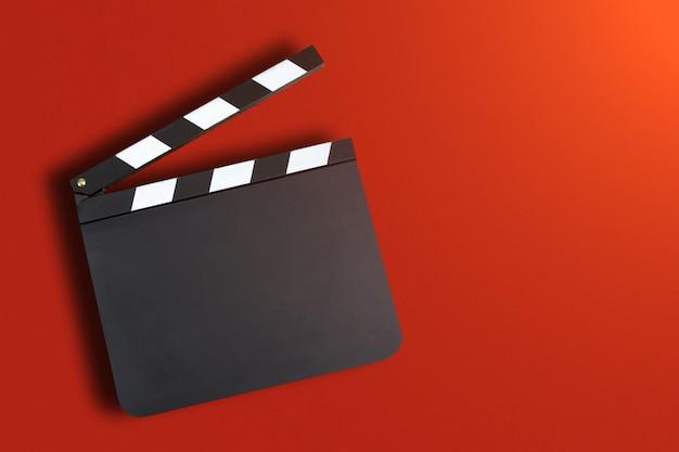 Leeres filmproduktionsscharnierventilbrett über rotem hintergrund mit co