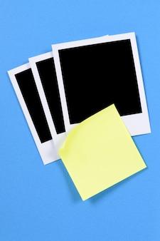 Leeres foto druckt mit gelber klebriger anmerkung auf einem blauen kraftpapierhintergrund.