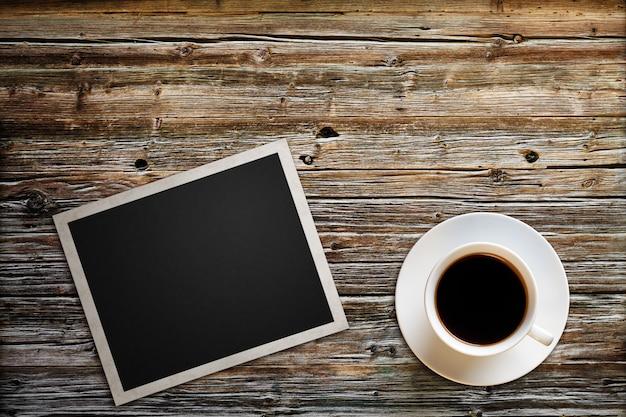 Leeres foto mit einer tasse kaffee liegt auf einem holztisch