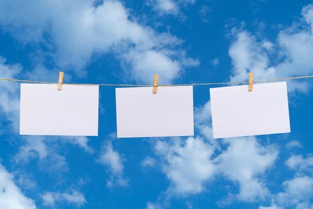 Leeres fotopapier, das an einer wäscheleine über wolken im hintergrund des blauen himmels hängt