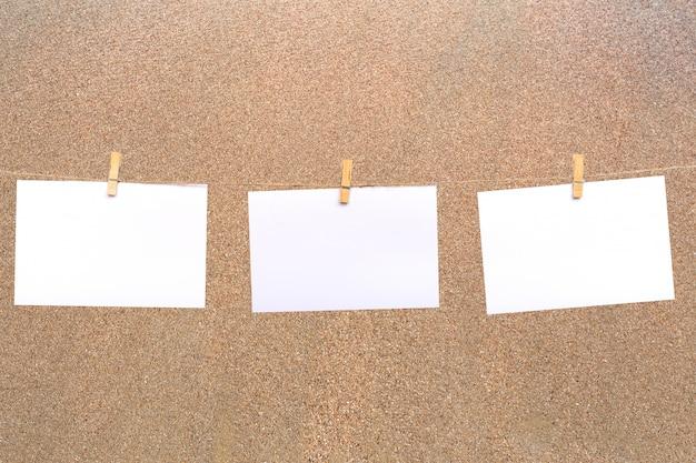 Leeres fotopapier, das an einer wäscheleine und über feinem sandbeschaffenheitshintergrund hängt