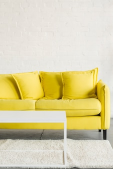 Leeres gemütliches gelbes sofa und weiße tabelle auf teppich gegen weiße wand