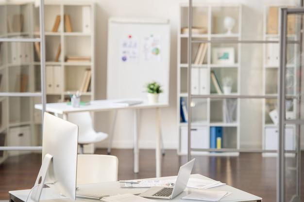 Leeres geschäftsbüro voller weißer möbel: schreibtisch mit finanzpapieren, computer und laptop