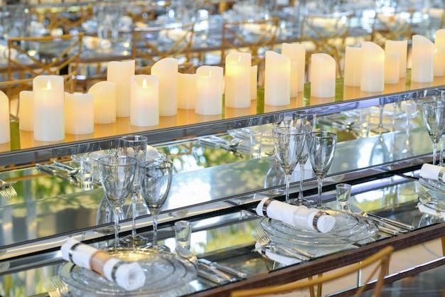 Leeres geschirr und kerzen im restaurant mit langem tisch