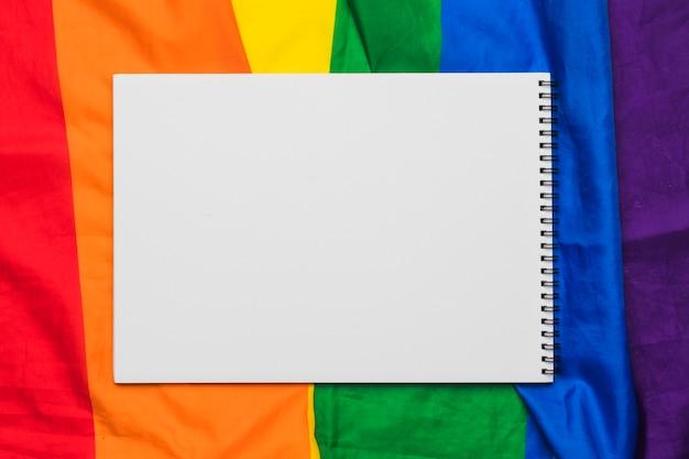 Leeres gewundenes notizbuch auf regenbogenflagge