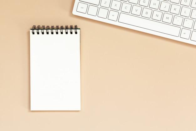 Leeres gewundenes notizbuch des arbeitsplatzes mit tastatur auf tabelle.
