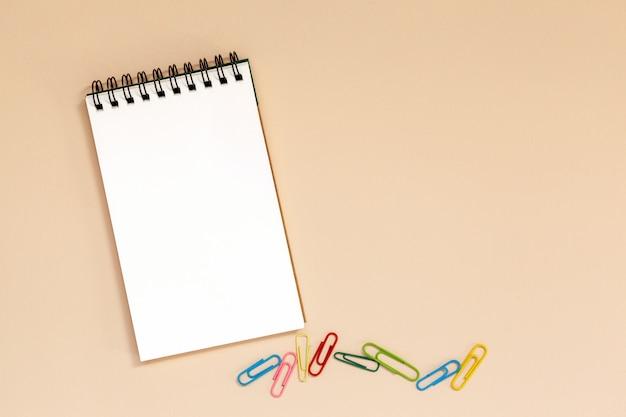 Leeres gewundenes notizbuch mit bunten klipps auf tabelle.