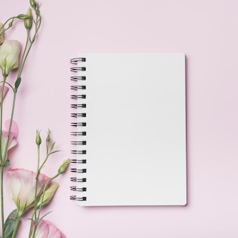 Leeres gewundenes notizbuch mit eustoma blüht gegen rosa hintergrund