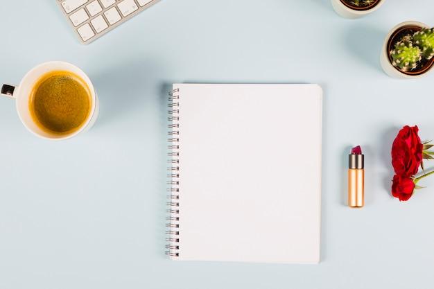 Leeres gewundenes notizbuch mit teetasse; tastatur; kaktuspflanze; rosen und lippenstift auf blauem hintergrund
