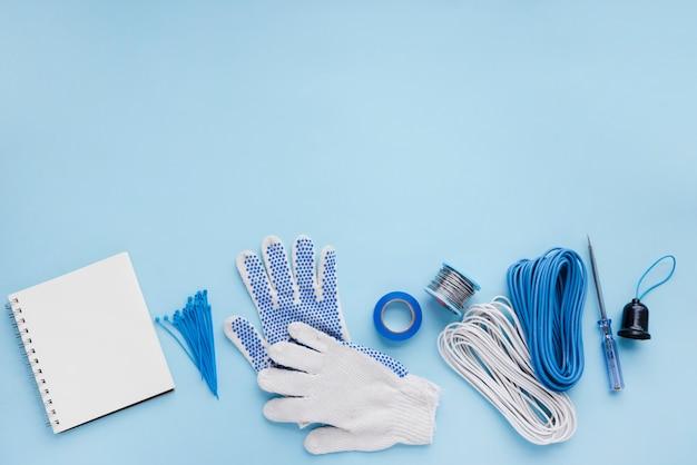 Leeres gewundenes notizbuch und elektrikerausrüstung auf blauer oberfläche