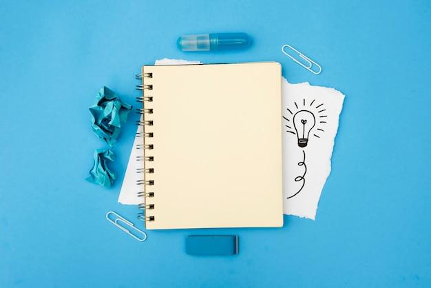 Leeres gewundenes tagebuch und briefpapierversorgungen mit hand gezeichneter glühlampe auf weißem kartenpapier über blauer oberfläche