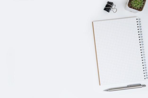 Leeres gitter zeichnet notizbuchseite auf weiße schreibtischtabelle. draufsicht, flach zu legen.