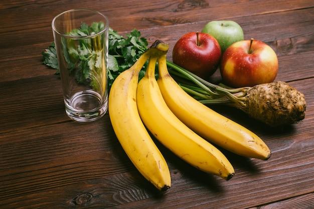 Leeres glas, äpfel, selleriewurzel und bananen auf einem dunklen holztisch