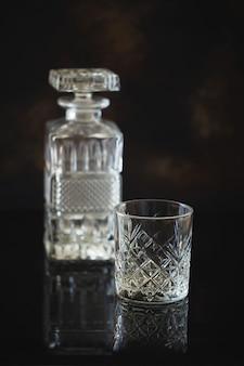 Leeres glas für whisky oder bourbon mit und eine kristallquadratkaraffe