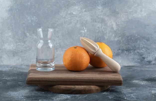 Leeres glas, holzreibahle und orangen auf holzbrett.