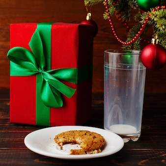 Leeres glas milch- und krümelkekse und ein geschenk unter dem weihnachtsbaum. die ankunft des weihnachtsmannes.