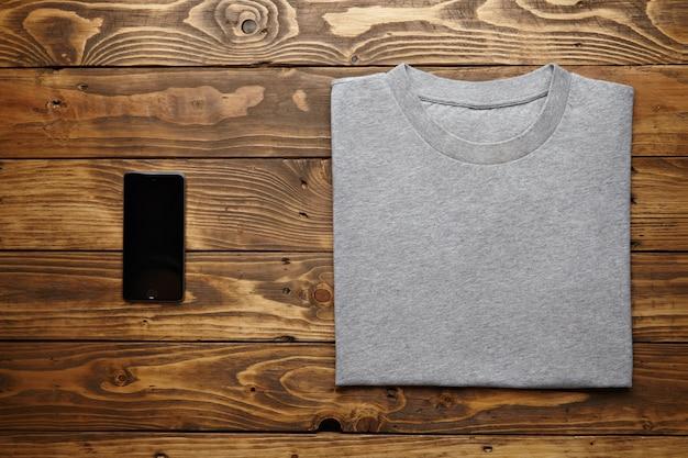 Leeres graues t-shirt genau gefaltet in der nähe von schwarzem smartphone-gadget auf rustikaler holztischplatte