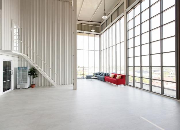 Leeres großes und großes indoor-industriedesign-fotografiestudio-wohnzimmer voller platz mit roter und grauer sofagarnitur mit holztisch in der nähe von glasfenstern mit kleinem büro im inneren.