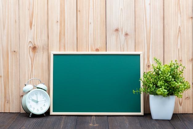 Leeres grünes chalkborad mit hölzernem rahmen und wenig dekorativem baum im weißen vasen- und weinlesewecker