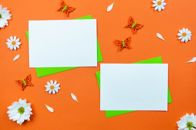 Leeres grußkartenmodell auf bunter orange oberfläche mit weißen gänseblümchenblumen und schmetterlingsdekoration