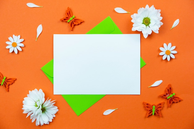 Leeres grußkartenmodell auf bunter orange oberfläche mit weißer gänseblümchenblumen- und schmetterlingsdekoration