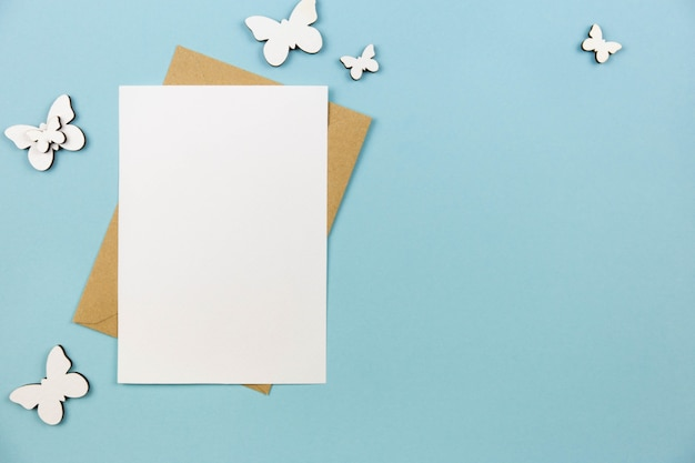 Leeres grußkartenmodell auf pastellblauer oberfläche mit weißer schmetterlingsdekoration