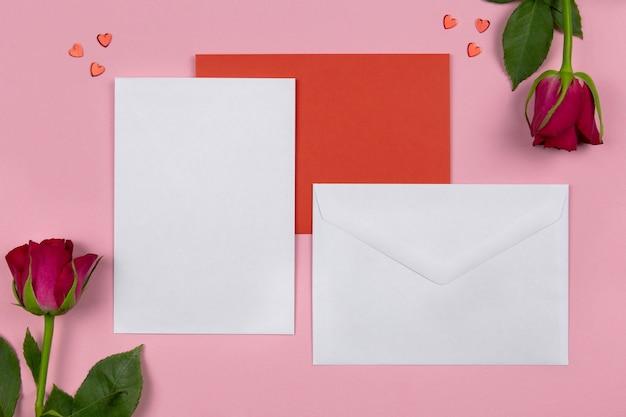 Leeres grußkartenmodell und umschlag auf rosa mit herzkonfetti für valentinsgrüße