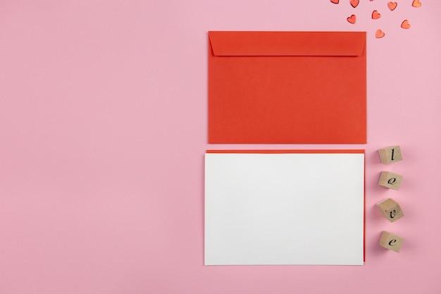 Leeres grußkartenmodell und umschlag auf rosa mit herzkonfetti für valentinstag, muttertag oder hochzeitsentwurf.