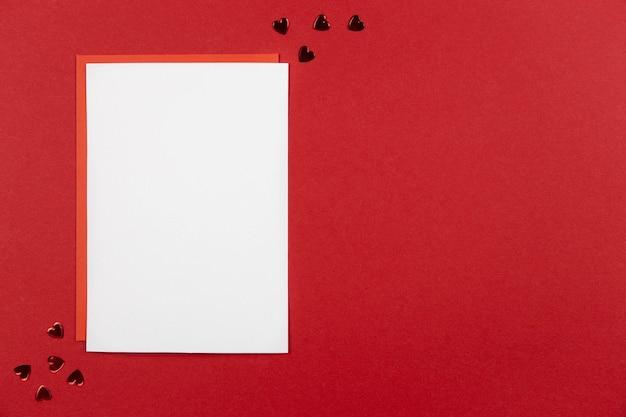 Leeres grußkartenmodell und umschlag auf rot mit herzkonfetti für valentinsgrüße