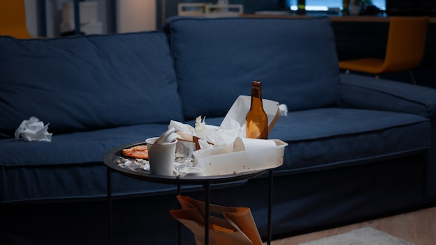 Leeres haus einer depressiven person mit unordentlichem tisch mit auf den boden geworfenen resten in unorganisiertem leben ...