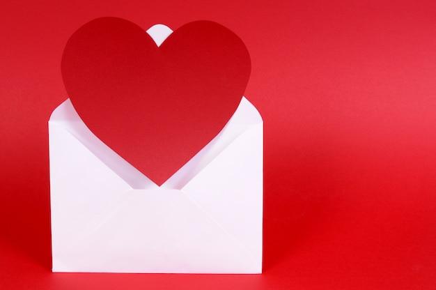 Leeres herz formte rote papierkarte mit weißem umschlag.