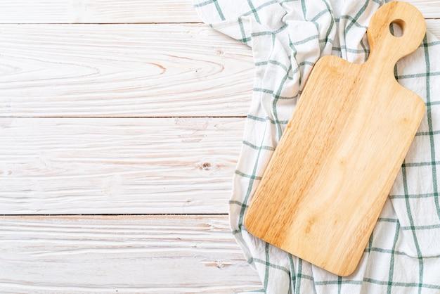 Leeres hölzernes brett des ausschnitts mit küchenstoff auf hölzernem hintergrund, draufsicht