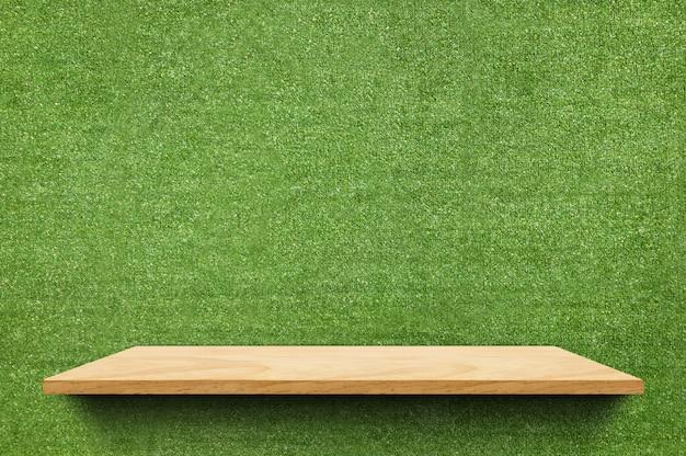 Leeres hölzernes brettregal am gefälschten wandhintergrund des grünen grases